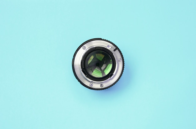 Camera lens with a closed aperture lie on texture of fashion pastel blue color paper Premium Photo