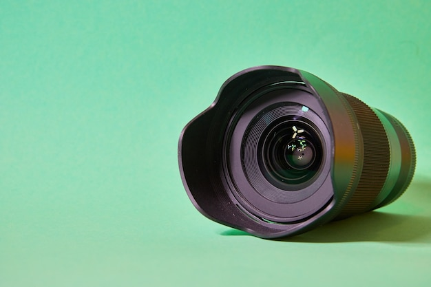 Camera lens with glare on the front lens on a green background