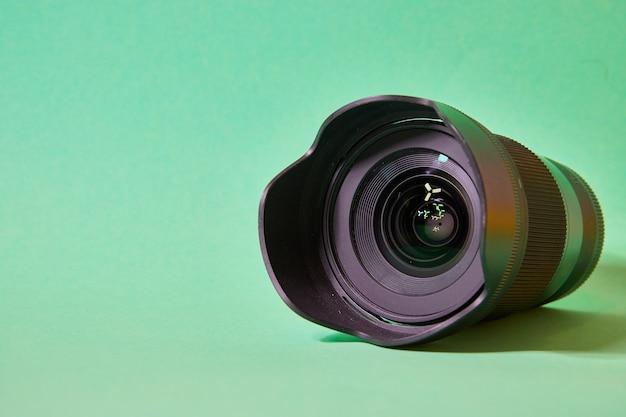 녹색 배경에 전면 렌즈에 눈부심이 있는 카메라 렌즈