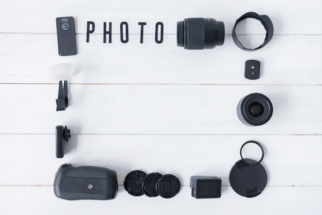 Camera lens with photography accessories and photo text arranged on white wooden table