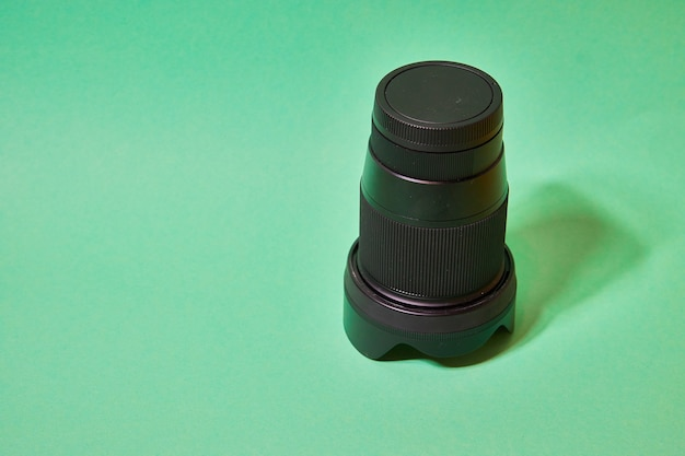 Camera lens with protective cover on a green background