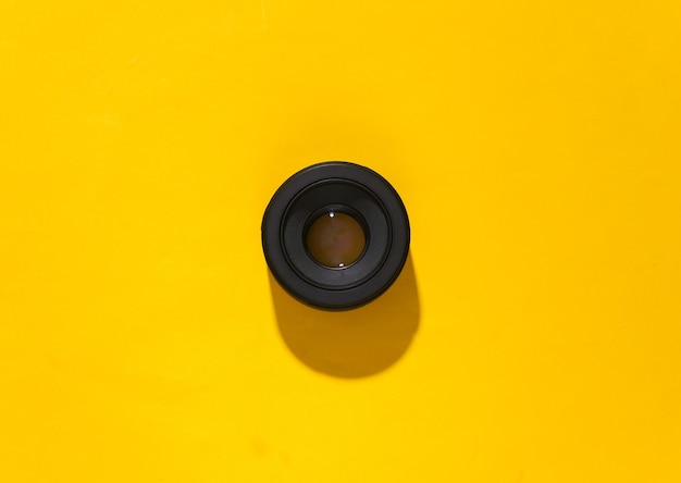 Camera lens on yellow bright background with deep shadow.