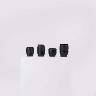 Camera lenses arranged on white block against isolated on white background