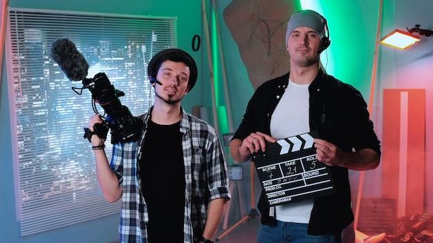 カメラマンとプロデューサーアシスタントがカメラに微笑んで、彼らの機器の映画用カメラを見せて...