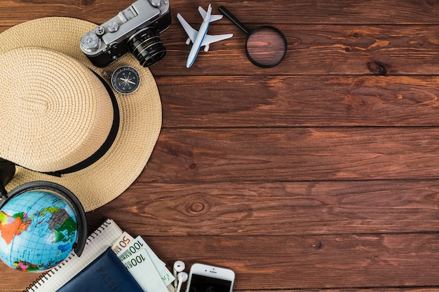 Camera, mobile, globe, straw hat and compass on wooden plank