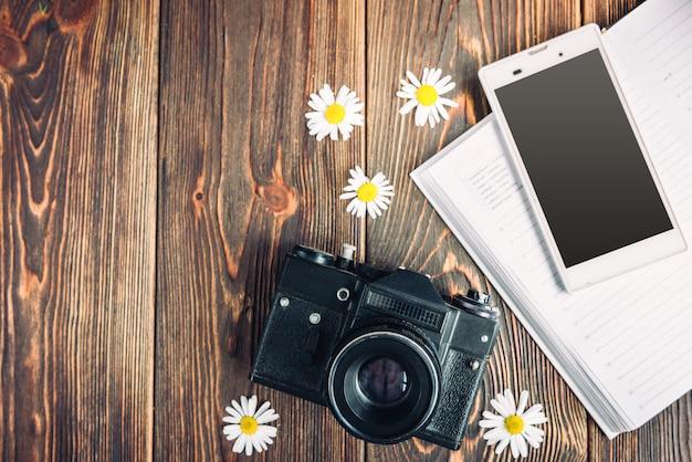 Фотоаппарат, ноутбук, мобильный телефон и полевые цветы на темном деревянном фоне. фриланс. заработок на фото.