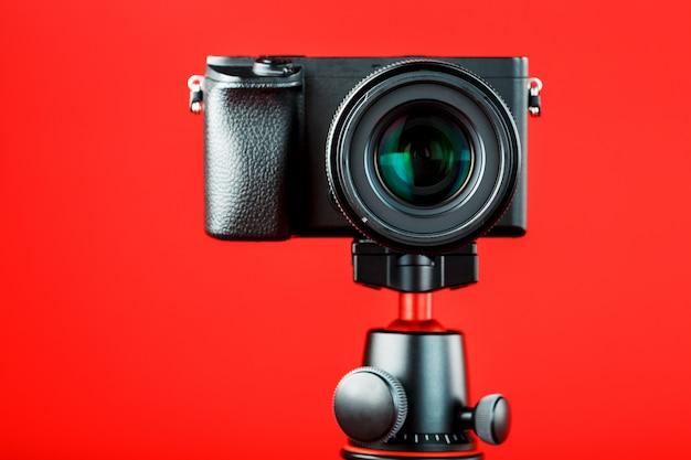 赤い背景の上のカメラ。ブログまたはレポート用にビデオと写真を記録します。