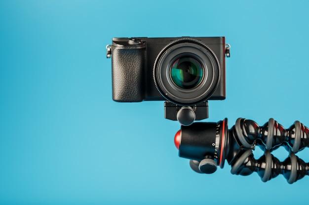 青色の背景に、三脚にカメラ。ブログまたはレポート用にビデオと写真を記録します。