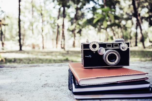 나무에 카메라 녹색 bokeh와 햇빛, 학교 개념을 다시 신선한 봄 녹색 정원 옆에 나무 플랫폼에서 책 스택 세.