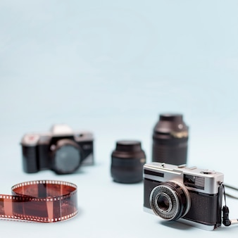 Camera; optical lens and rolled up film stripe on blue background
