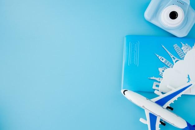 Камера, паспорт и самолет на голубом фоне. концепция лета или отпуска. скопируйте пространство.