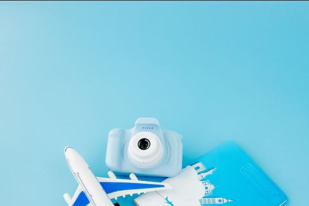 카메라, 여권 및 밝은 파란색 배경에 비행기 여름 또는 휴가 개념. 공간을 복사하십시오.