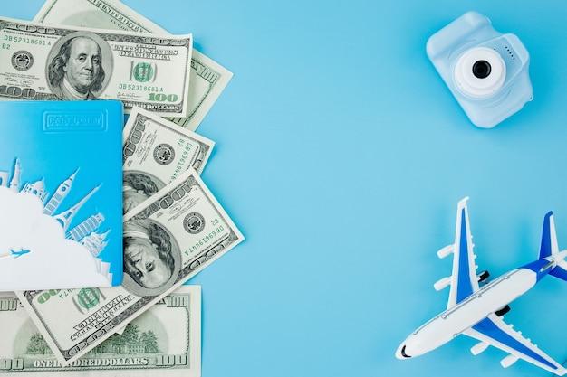 밝은 파란색의 카메라, 여권, 달러 및 비행기