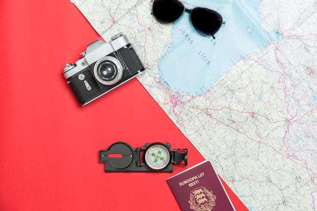 Macchina fotografica e passaporto vicino a bussola e mappa