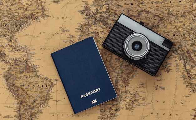 Camera and passport on old map. travel, adventure concept