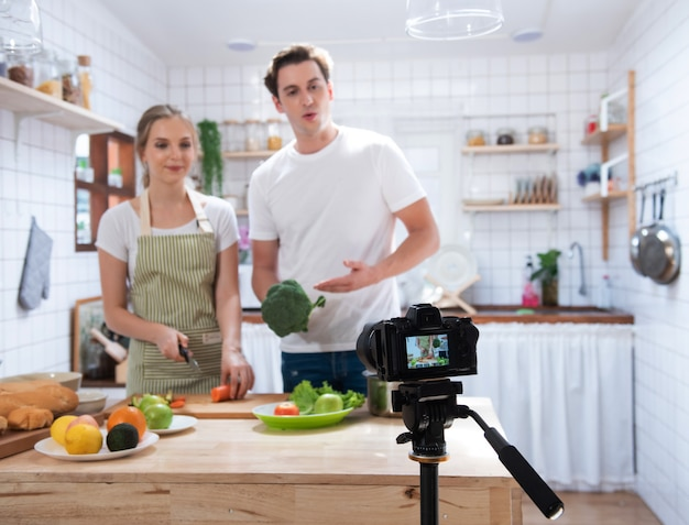 Camera record video blog of couple cook in kitchen