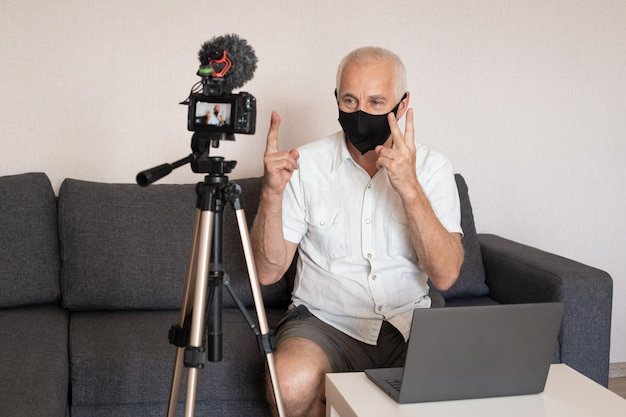 Camera recording video blog of senior male blogger in mask at home, blogging, videoblog and people concept