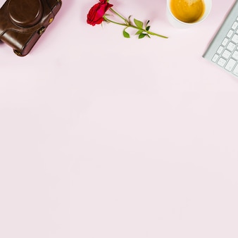 Camera; rose; tea cup and keyboard on pink background