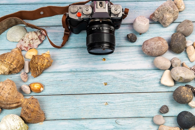 Camera and seashells on a blue wooden background.marine theme