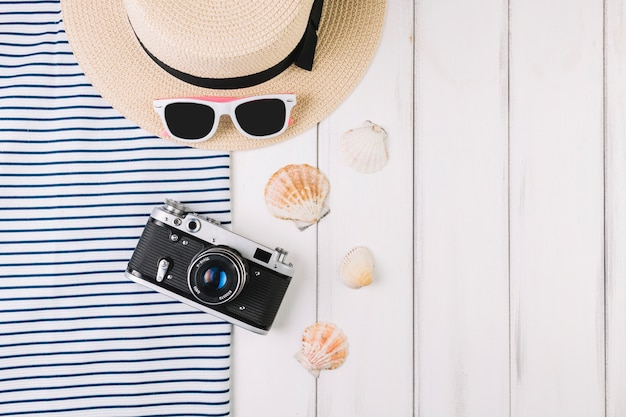 Camera and seashells near hat and sunglasses