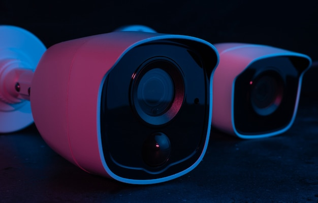 Camera security on dark surface in pink light.