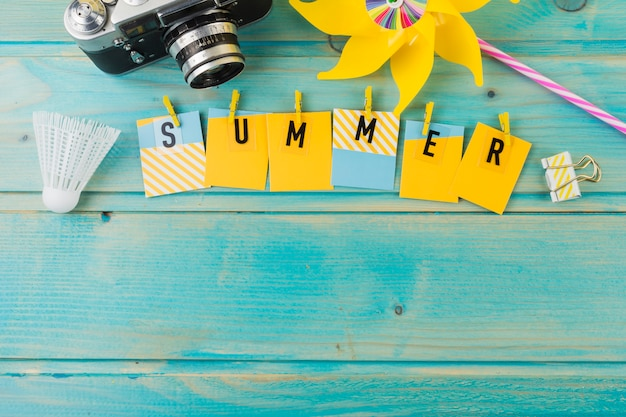 Camera; shuttlecock; pinwheel and summer with clothespin on wooden desk