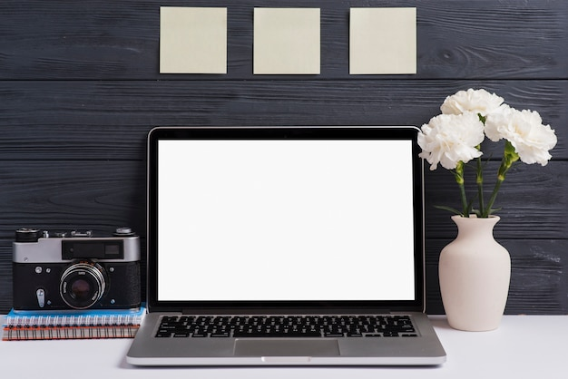 Camera; spiral notebook; flower vase and an open white blank laptop on desk against wooden background