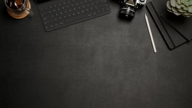 Camera and tablet keyboard on a black table