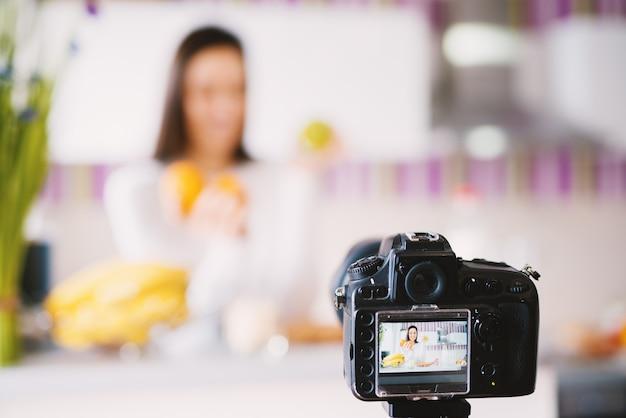 Камера фотографируя очаровательная молодая дама держа плодоовощ.
