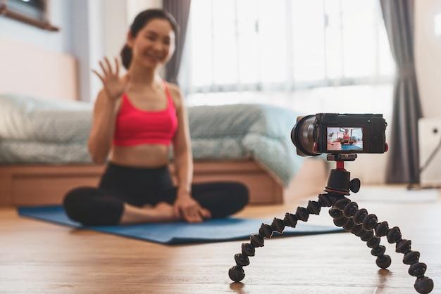 寝室で自宅からヨガを練習しているアジアの女性のビデオとライブを撮るカメラ