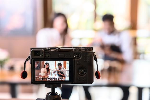 一杯のコーヒーを提示し、コーヒー豆の匂いを嗅ぐ2人のアジアのバリスタにビデオを撮るカメラ