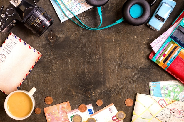 Camera, touristic maps, passport, toy car, coffee, headphones, wallet with credit cards, euro banknotes and coins on a black desk. travel background.