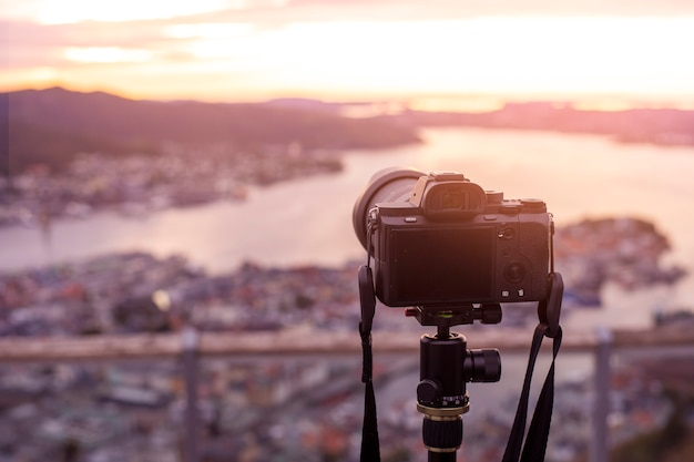 A camera on tripod  is photographing  beautiful view at twilight