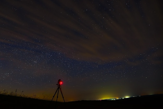 The camera on the tripod takes pictures of stars of open space in the night sky with clouds.