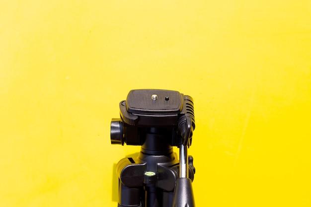 Camera tripod over yellow wall.