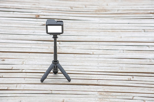 Camera and video with small black stand on a bamboo floor.