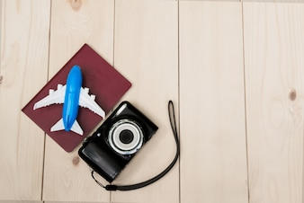 Camera with air plane and notebook for travel wooden table background