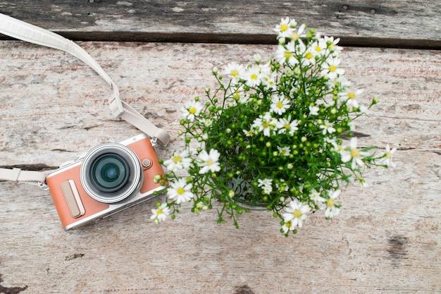 Camera with white flower vase on old brown wooden desk.