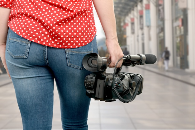 Camera woman holding his professional camcorder in the street