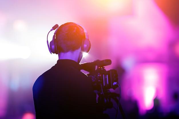 Cameraman at event. purple background.