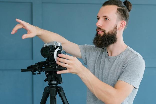 カメラマンの指示。ビデオ撮影プロセス。カメラを持って、セットを指で指している男性。