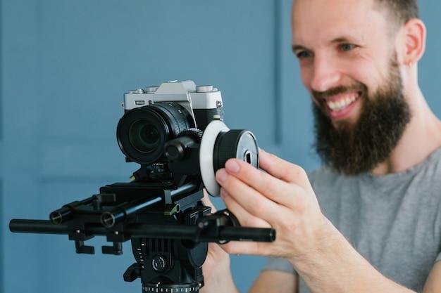 カメラマンのライフスタイルとビデオ撮影の趣味。ホルダーと三脚のカメラを使用して放送やブログのコンテンツを作成する男。現代の機器とツールのコンセプト。