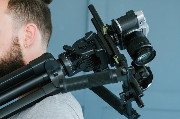 カメラマンの職業。ライフスタイルと趣味。肩にカメラを持っている男。ビデオストリーミングの概念のための最新の機器とツール。