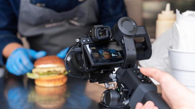 햄버거를 만드는 요리사, stadicam에 카메라를 녹화하는 카메라맨. 푸드 트럭