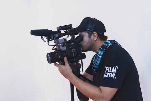 白い背景の上の彼のカメラでカメラマン撮影映画のシーン