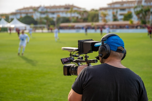 Cameraman shooting live broadcast from soccer game to television and internet