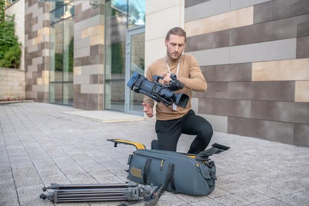 Кинооператор вынимает оборудование из кейса