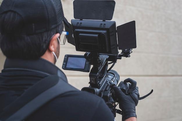 Covid19のカメラでフィルムシーンを撮影するための抗ウイルスマスクkn95を持つカメラマン