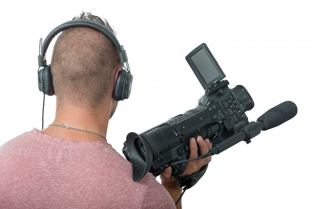 Cameraman with professional camcorder and headphones, back view
