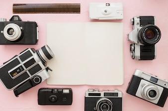 Cameras and film strip around notebook